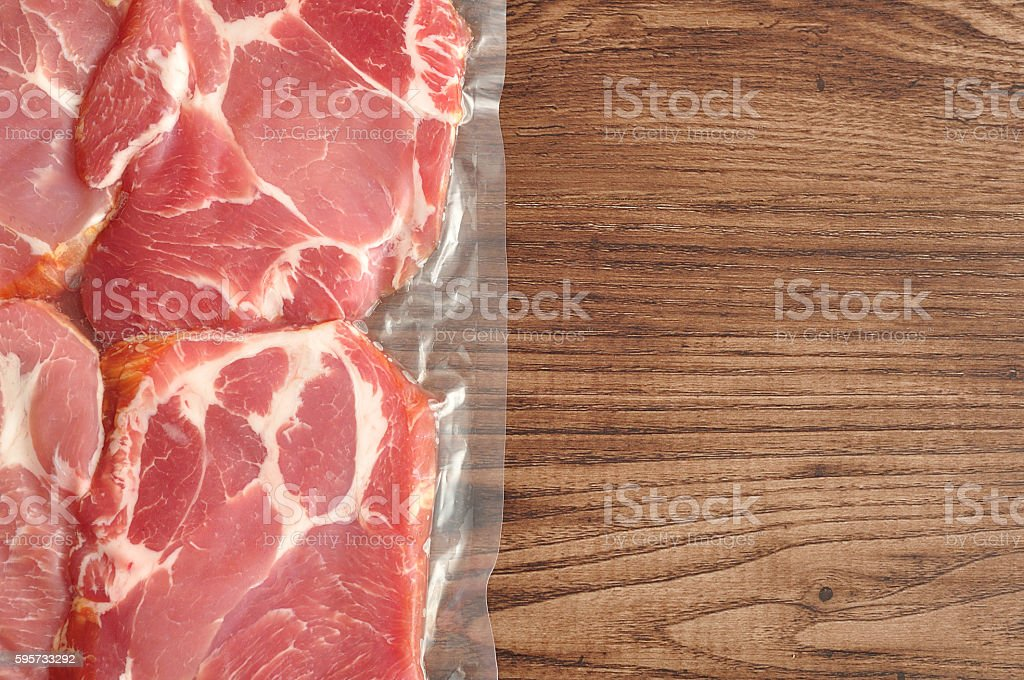 Vacuum packed meat displayed on a wooden background stock photo