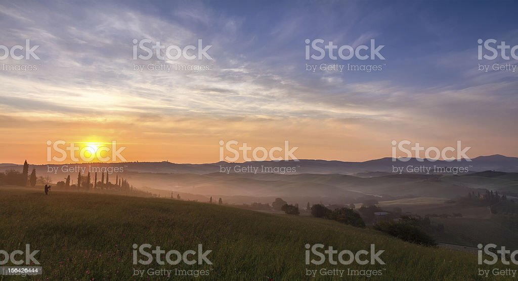 Val d'Orcia after sunrise with photographer, Tuscany, Italy royalty-free stock photo