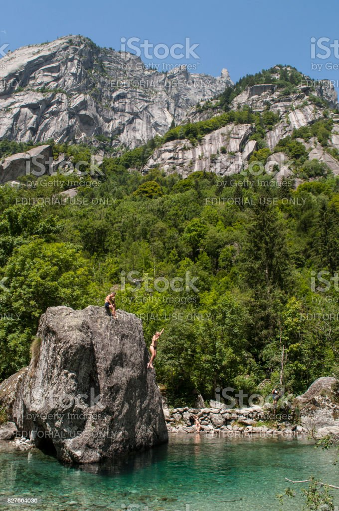 Val Masino: a girl diving from a rock called the Bidet of the Countess in Val di Mello, green valley surrounded by granite mountains and forest trees stock photo