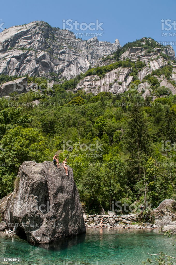 Val Masino: a girl waiting for diving from a rock called the Bidet of the Countess in Val di Mello, green valley surrounded by granite mountains and forest trees stock photo