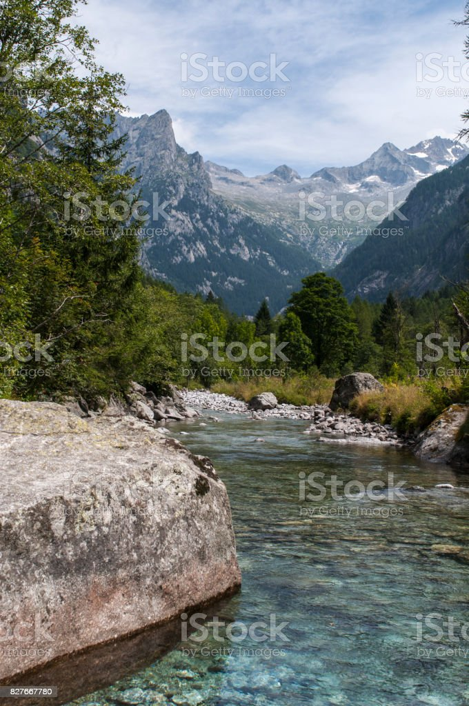Val Masino: creek and rocks of the Mello Valley, Val di Mello, a green valley surrounded by granite mountains and forest trees stock photo