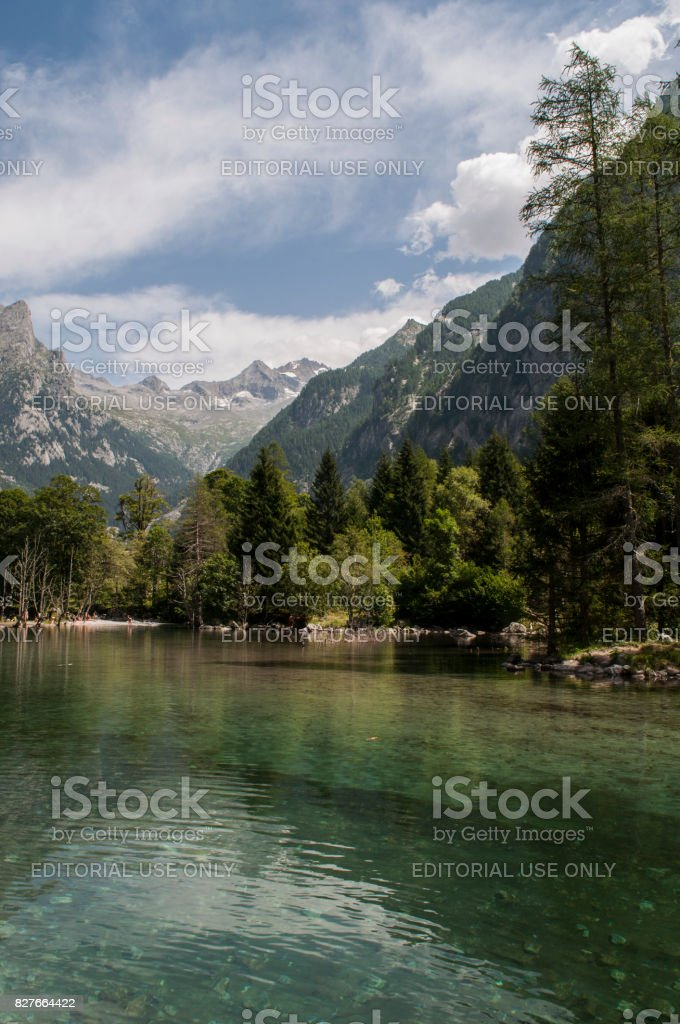 Val Masino:  the crystal clear water of the alpine lake in the Mello Valley, Val di Mello, a green valley surrounded by granite mountains and forest trees stock photo