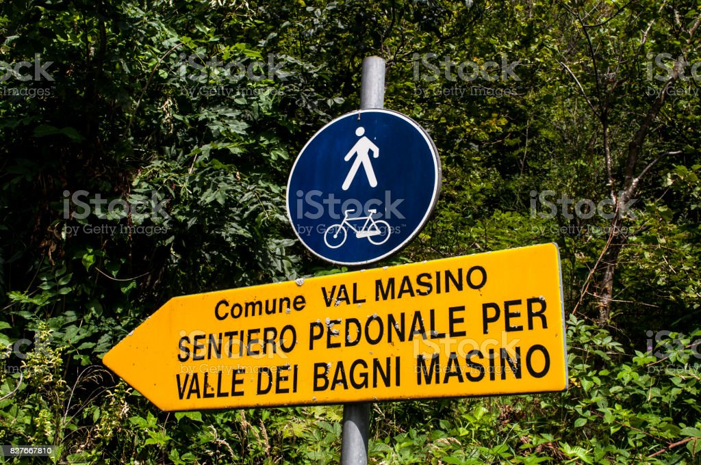 Val Masino: the sign of the footpath for the Valle di Bagni Masino, a green valley surrounded by granite mountains and forest trees stock photo