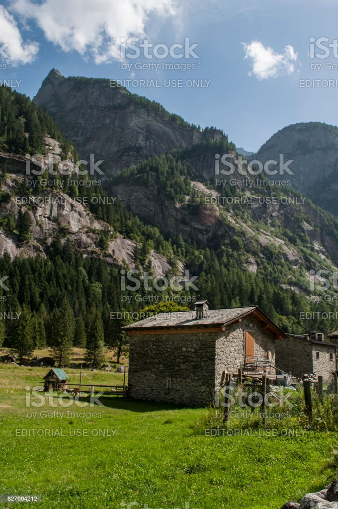 Val Masino: view of a house in the Mello Valley, Val di Mello, a green valley surrounded by granite mountains and forest trees stock photo