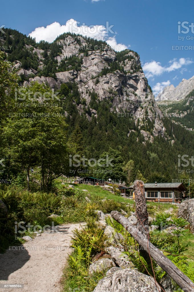 Val Masino: view of the footpath leading to a mountain retreat in the Mello Valley, Val di Mello, a green valley surrounded by granite mountains and forest trees stock photo