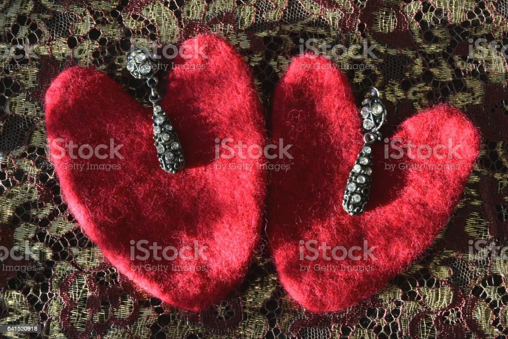 Valentine and earrings lying on colored laces stock photo