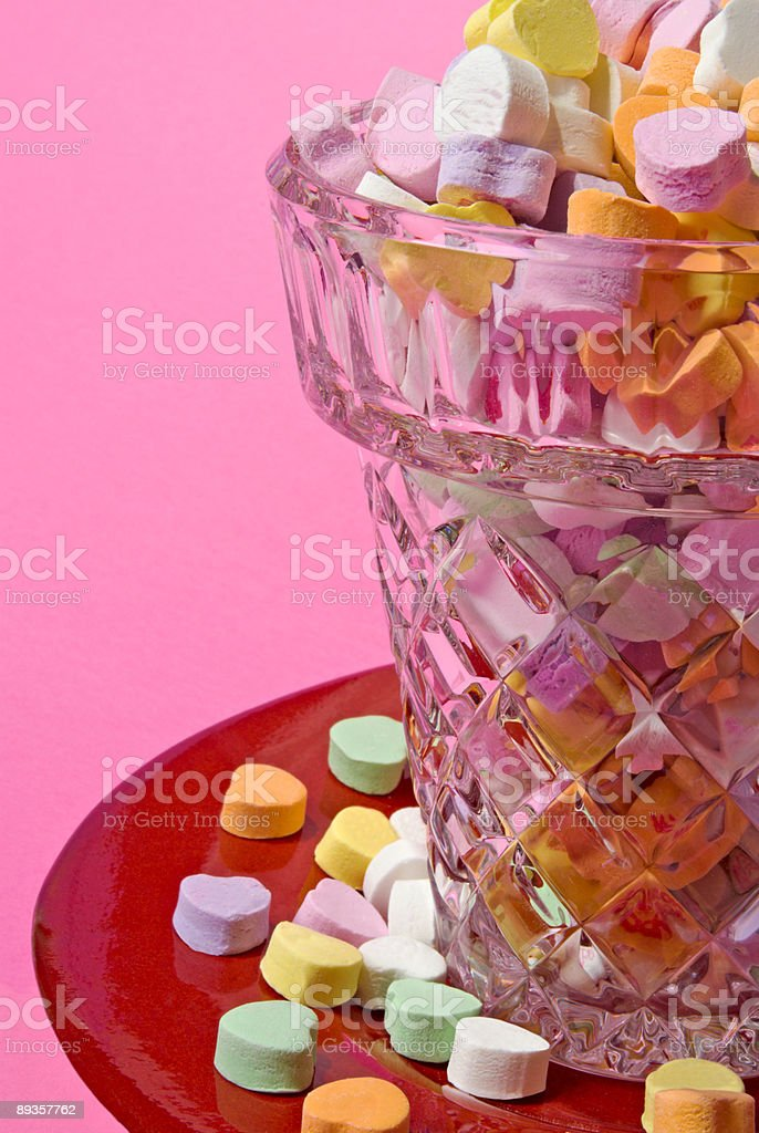 Valentine candy hearts in a crystal glass and pink background royalty-free stock photo