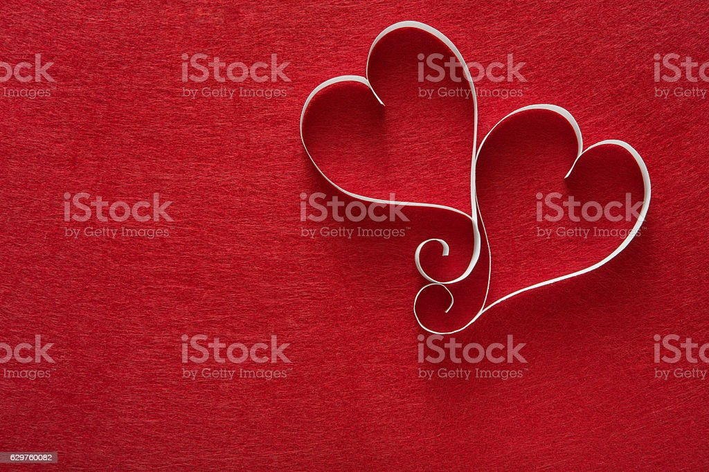 Valentine day background, handmade paper hearts on red felt stock photo