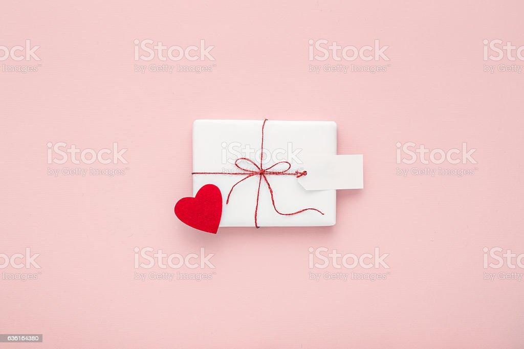 Valentine day composition: white gift box, felt heart, greeting label. stock photo