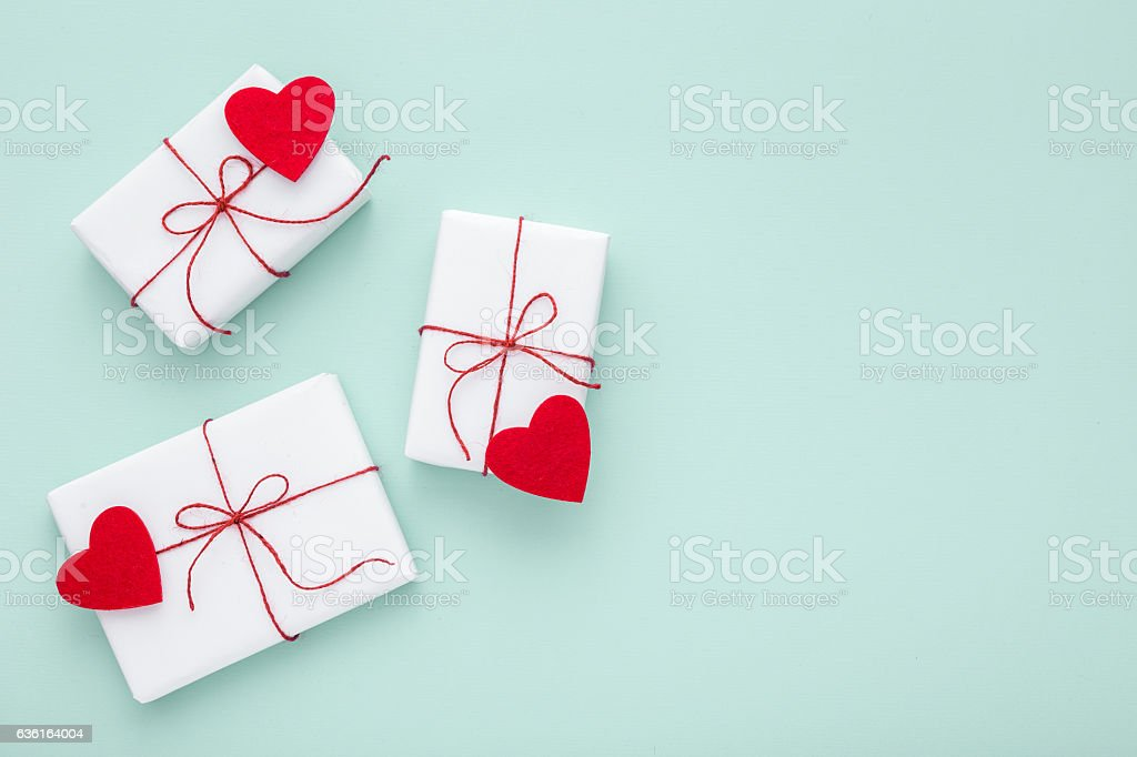 Valentine day composition: white gift boxes, felt hearts, copy space. stock photo