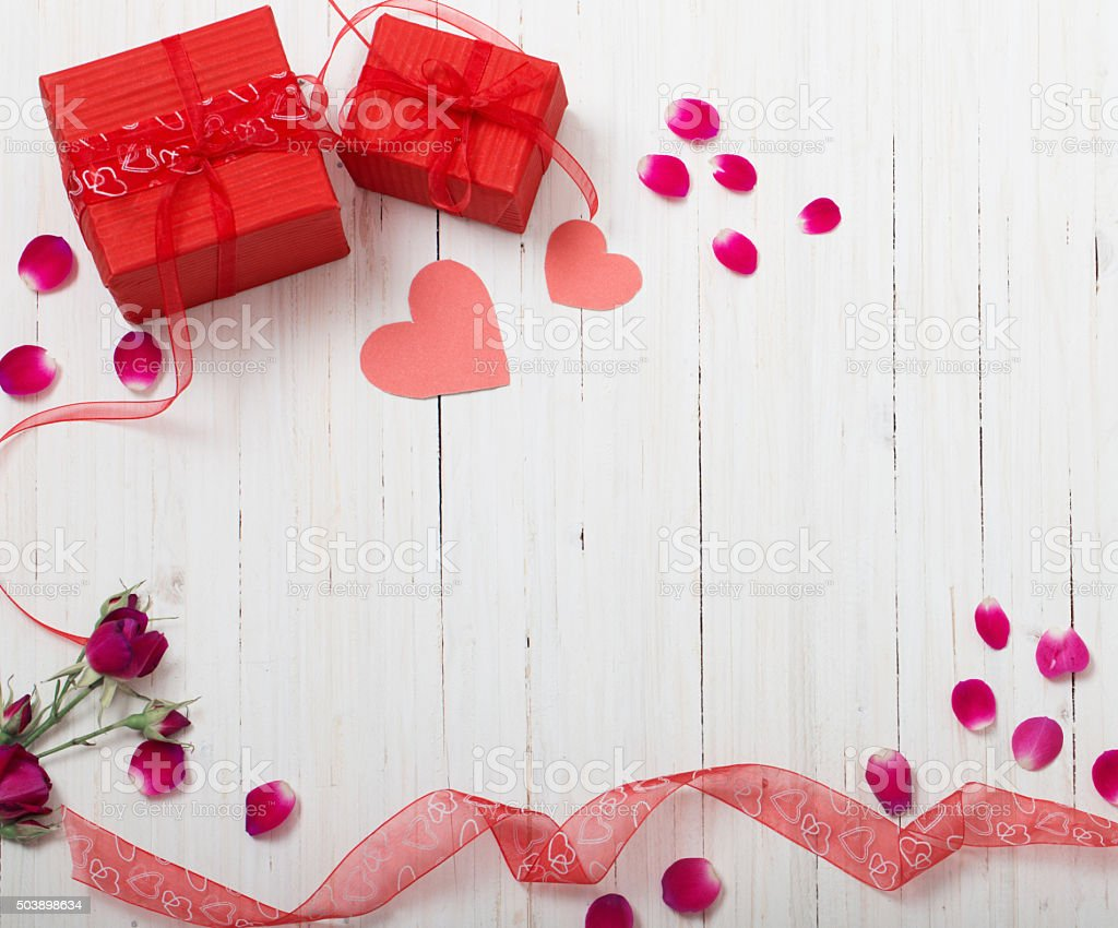 valentine gift box and red heart shapes on wooden board stock photo