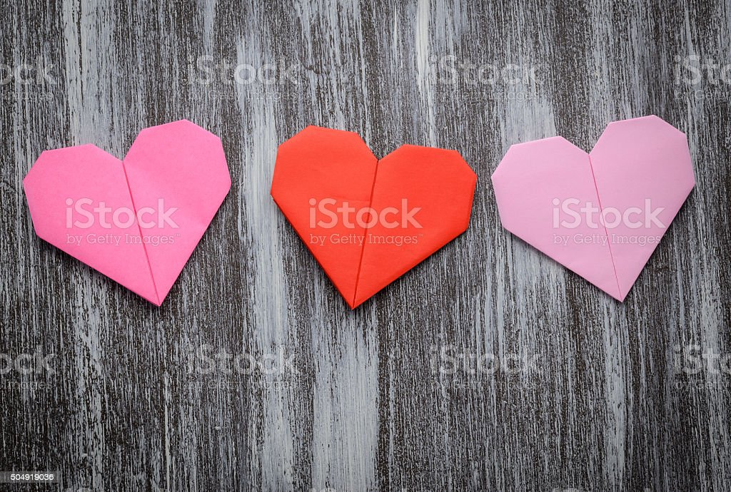 Valentine greeting paper folded origami love heart on wooden bac stock photo
