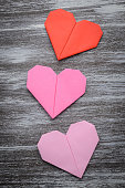 Valentine greeting paper folded origami love heart on wooden bac