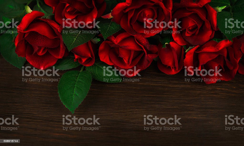 Valentine red rose bouquet background on rustic wooden table stock photo