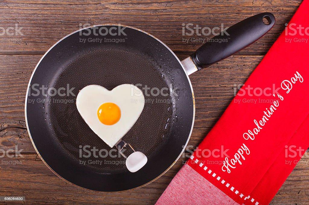 Valentine's breakfast Fried egg in iron form heart crop stock photo