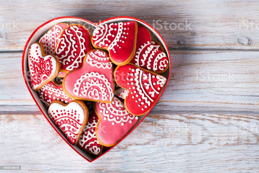 Valentine's cookies in a heart shape box on wooden table stock photo
