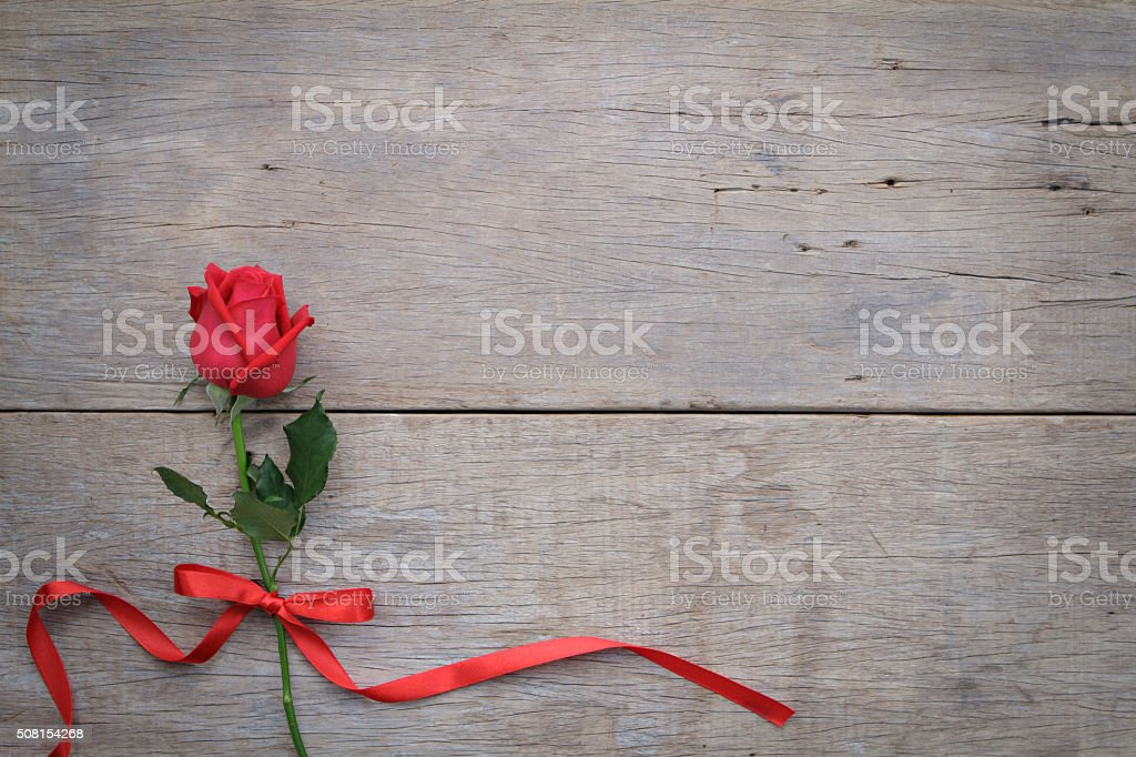 Valentines day background with red rose and ribbon on wooden. stock photo