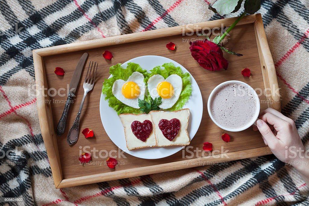 Valentines day breakfast in bed with heart-shaped eggs, jam stock photo