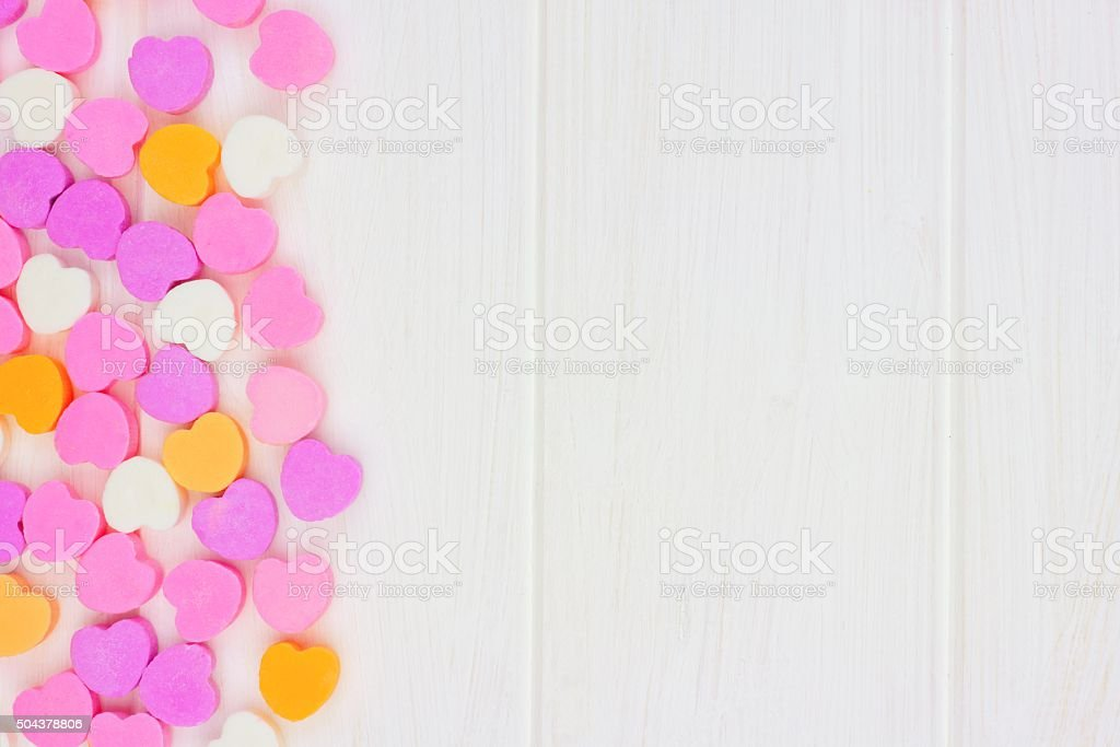 Valentines Day candy hearts side border over white wood stock photo
