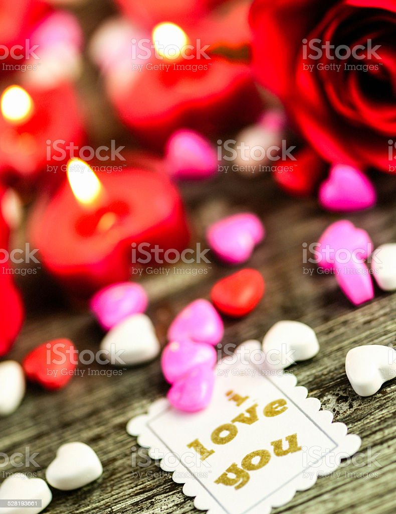 Valentine's Day candy hearts with roses and candles stock photo