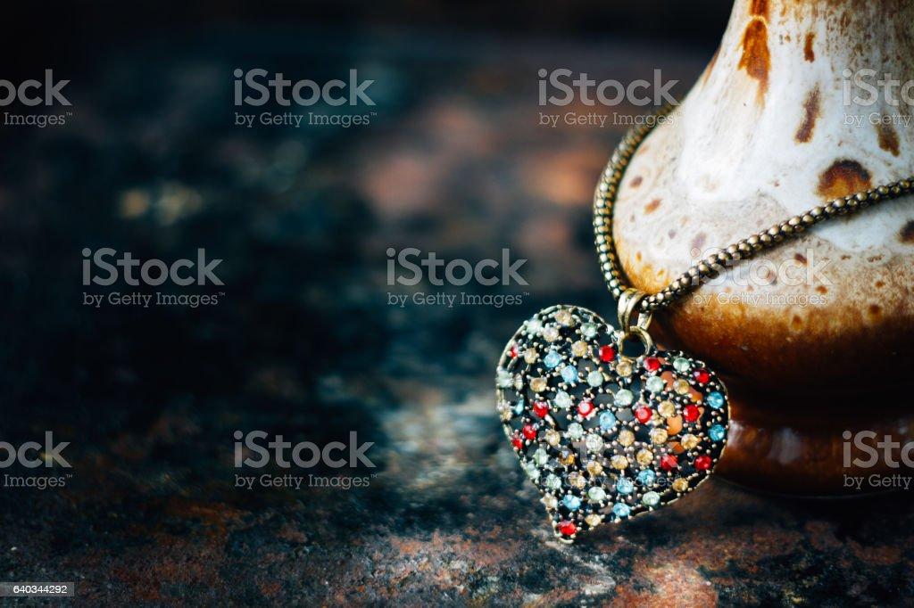 Valentine's day concept - heart jewellery pendant on black background. stock photo
