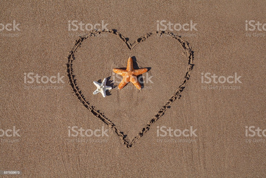 valentine's day concept with starfish and drawn heart on beach. stock photo