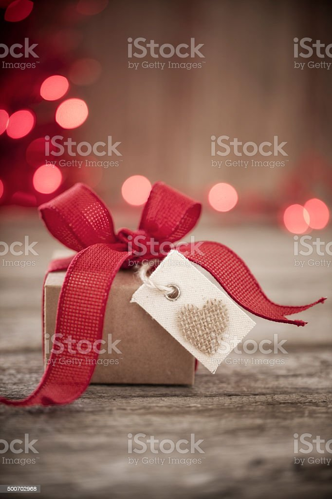 Valentine's day gift, burlap heart tag, red ribbon, on wood stock photo