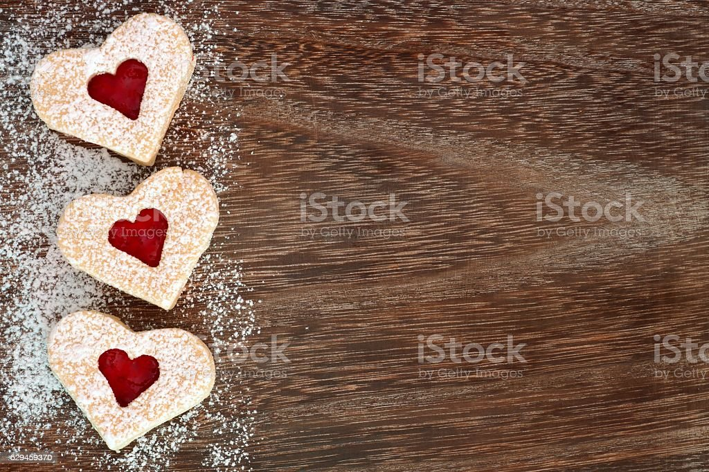 Valentines Day heart cookies border with powdered sugar over wood stock photo
