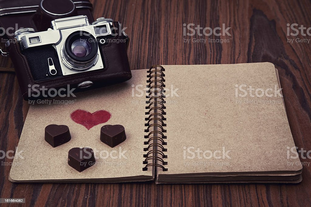 Valentine's Day - heart shape chocolates and camera on notebook royalty-free stock photo