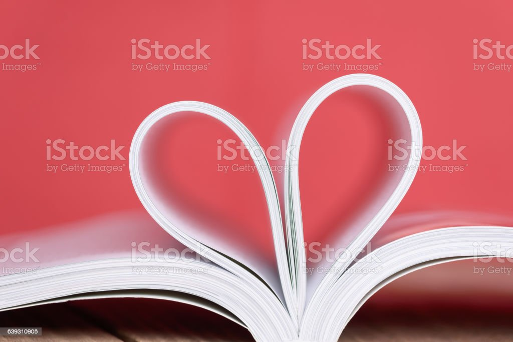 Valentine's day heart shape from book pages with red background. stock photo