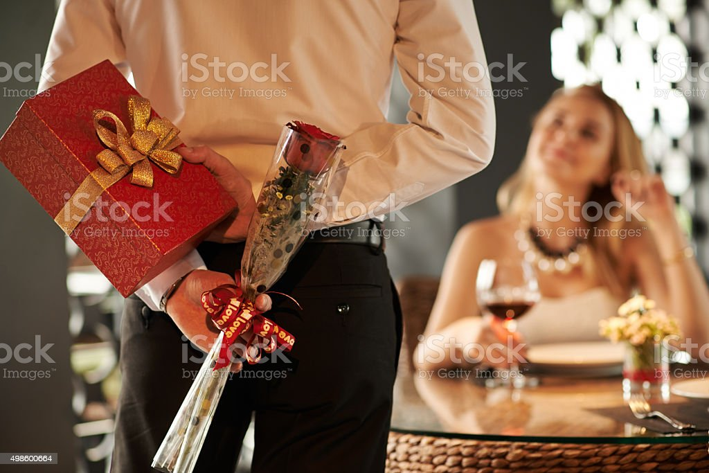 Man hiding red rose and gift for his girlfriend behind his back