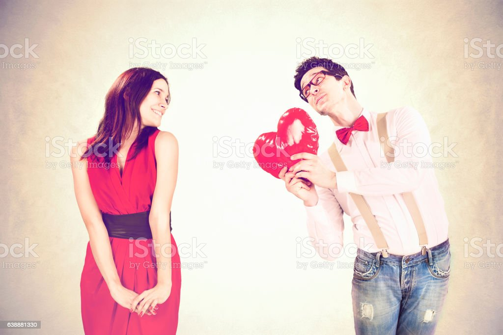 Valentine's Day, romantic boy gives a heart to his girlfriend stock photo