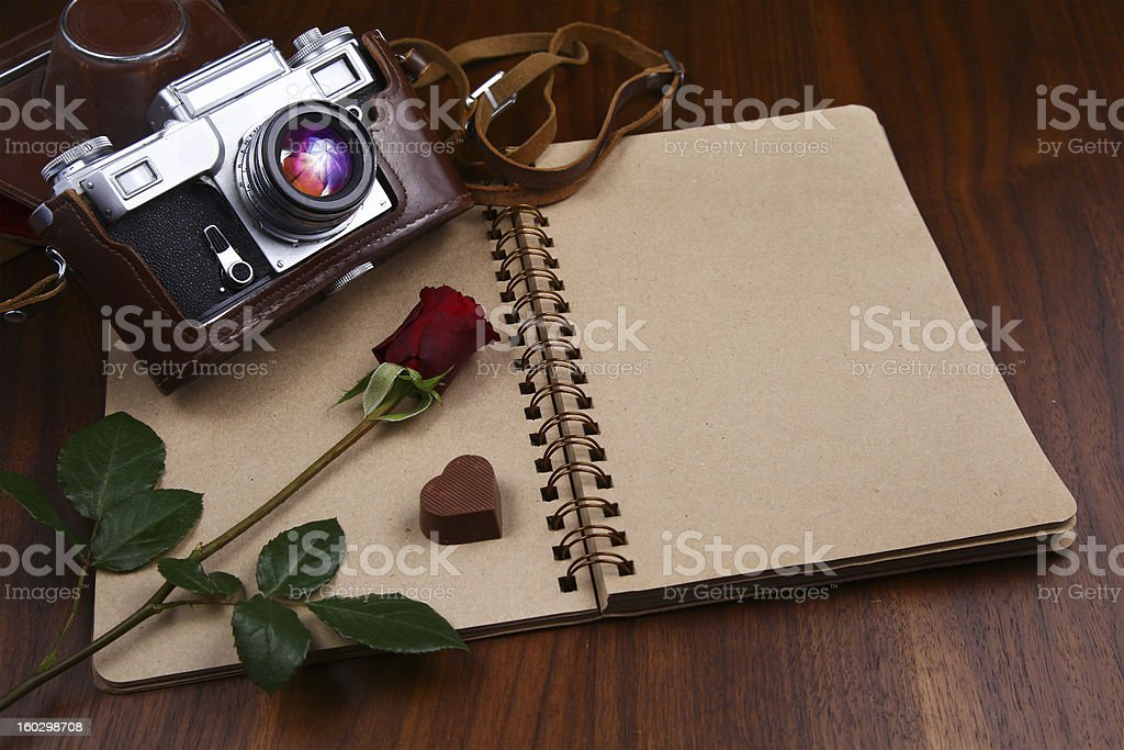 Valentine's Day - Rose, chocolates and camera on notebook royalty-free stock photo