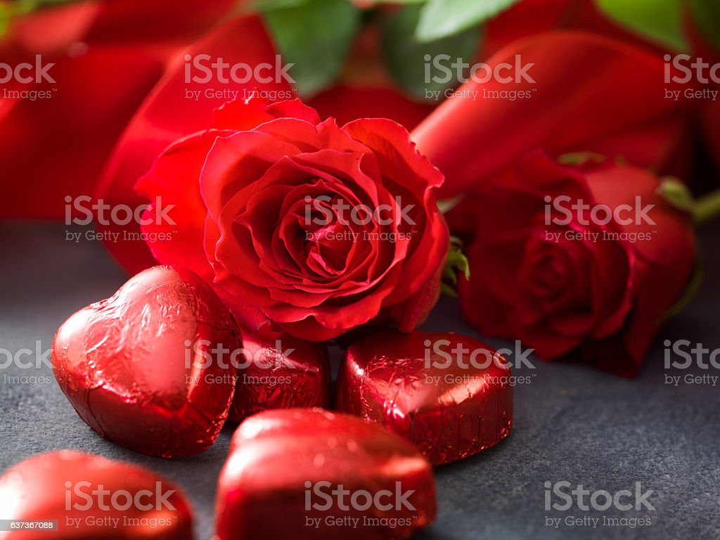 Valentine's day roses with red ribbon and hart shaped chocolate stock photo
