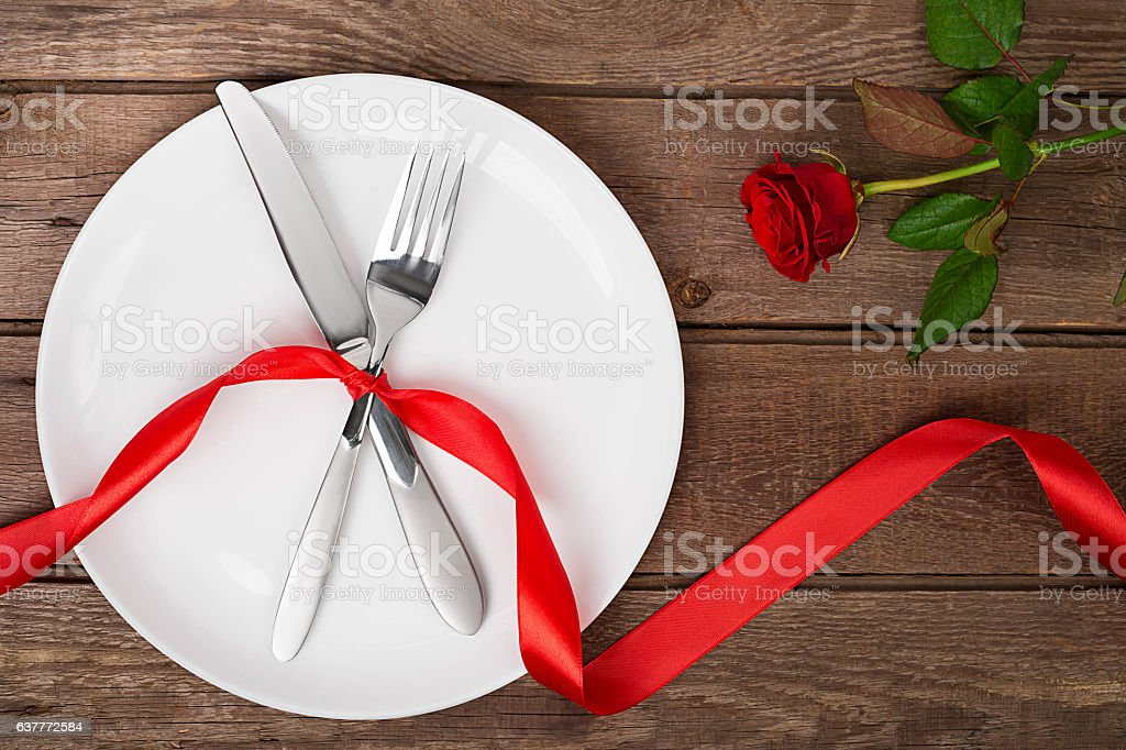 Valentines day table setting with plate, fork, knife, ribbon and...