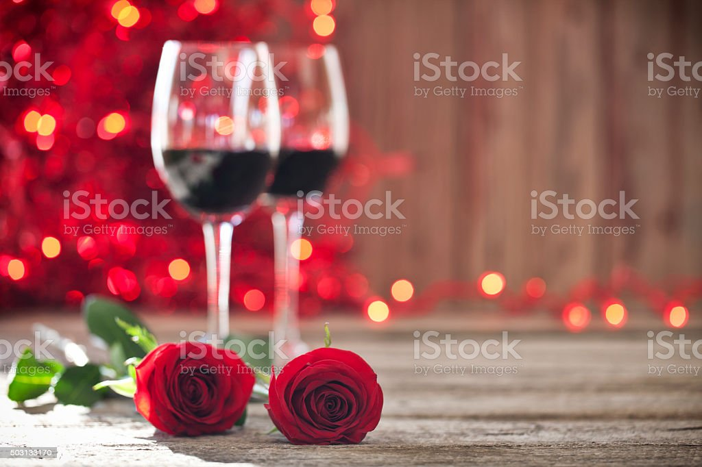Valentine's day wine, red roses on old wood rustic background stock photo