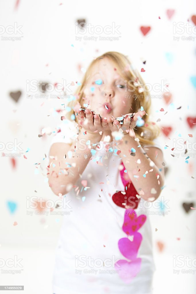 Valentines girl blowing heartshaped confetti royalty-free stock photo