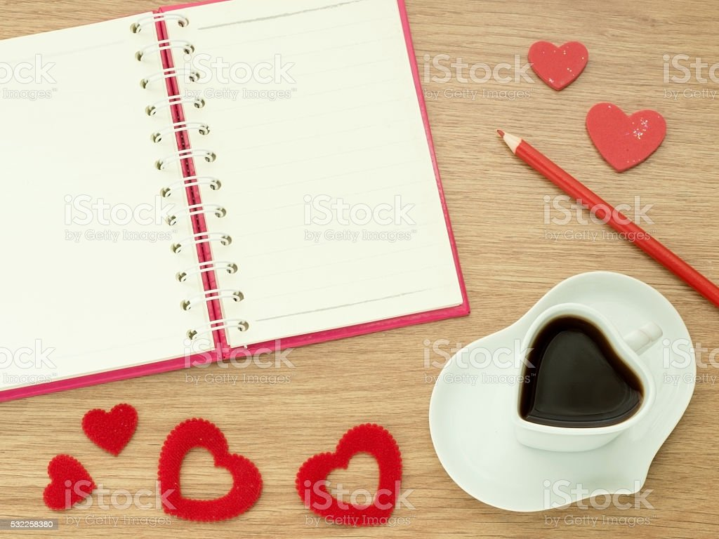 Valentines heart cup coffee, red hearts, book pencils wood floor stock photo