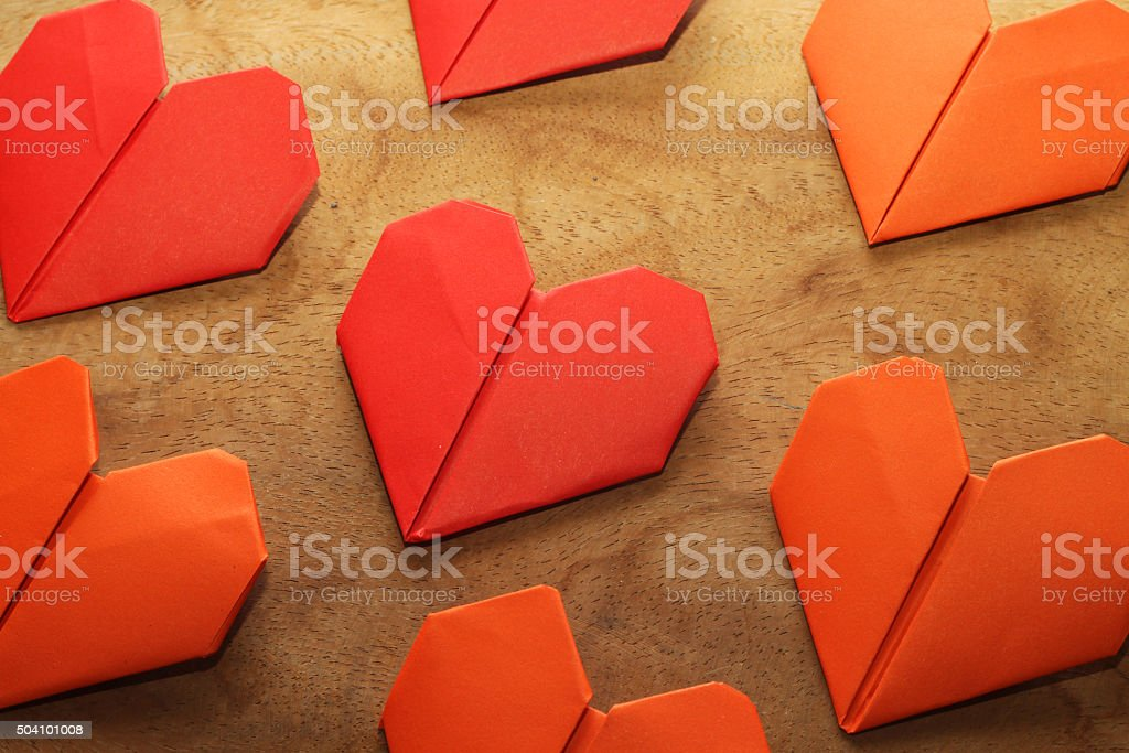 Valentine's heart shaped folded papers on wood background stock photo