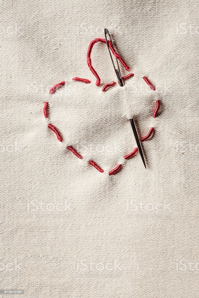 Valentines heart symbol made of red thread over canvas backgroun stock photo