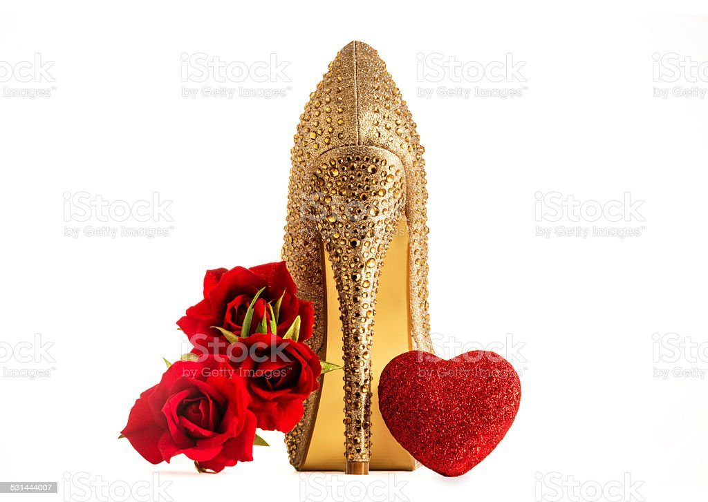 Valentinie present.Sexy gold heel with red roses and chocolate heart. stock photo