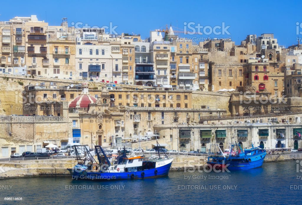 Valetta, Malta: Skyline from Harbor with Blue Fishing Boats stock photo