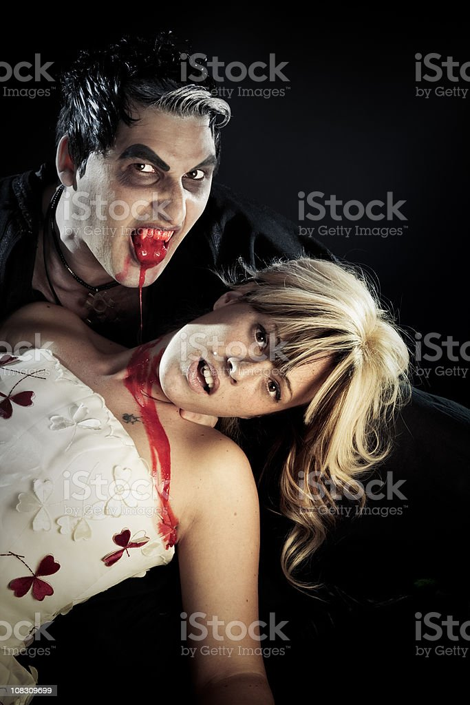 Vampire biting a young woman. royalty-free stock photo