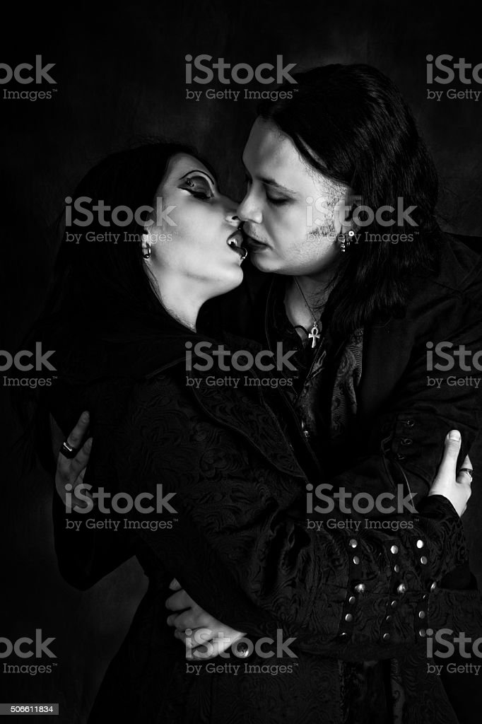 Vampire couple almost kissing, B&W vertical shot with added detail. stock photo