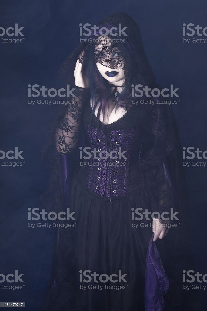 Vampire in lace cloak and fog. stock photo