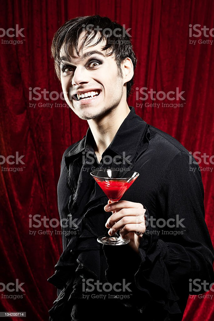 Vampire is offering a bloody drink while smiling dangerously stock photo