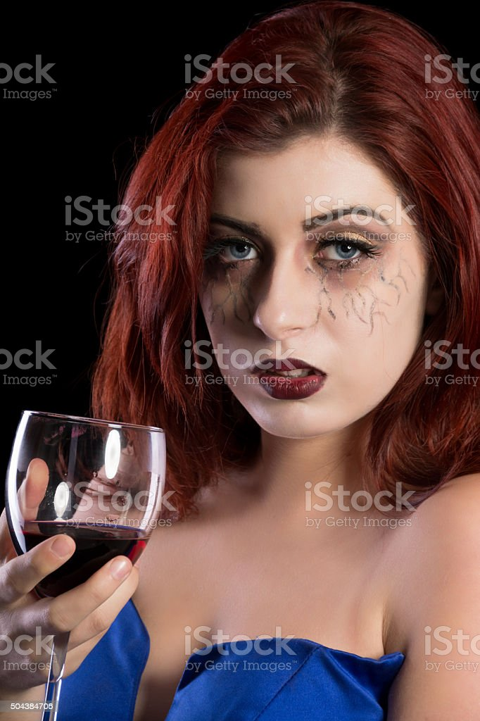 Vampire, red haired holding a wine glass, closeup. stock photo