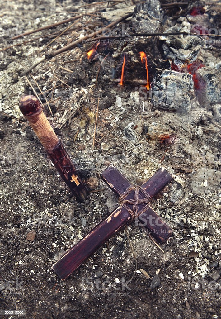 Vampire still life with wooden cross and stake by fire stock photo