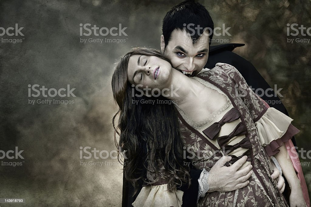 Vampire sucking blood from woman's neck stock photo