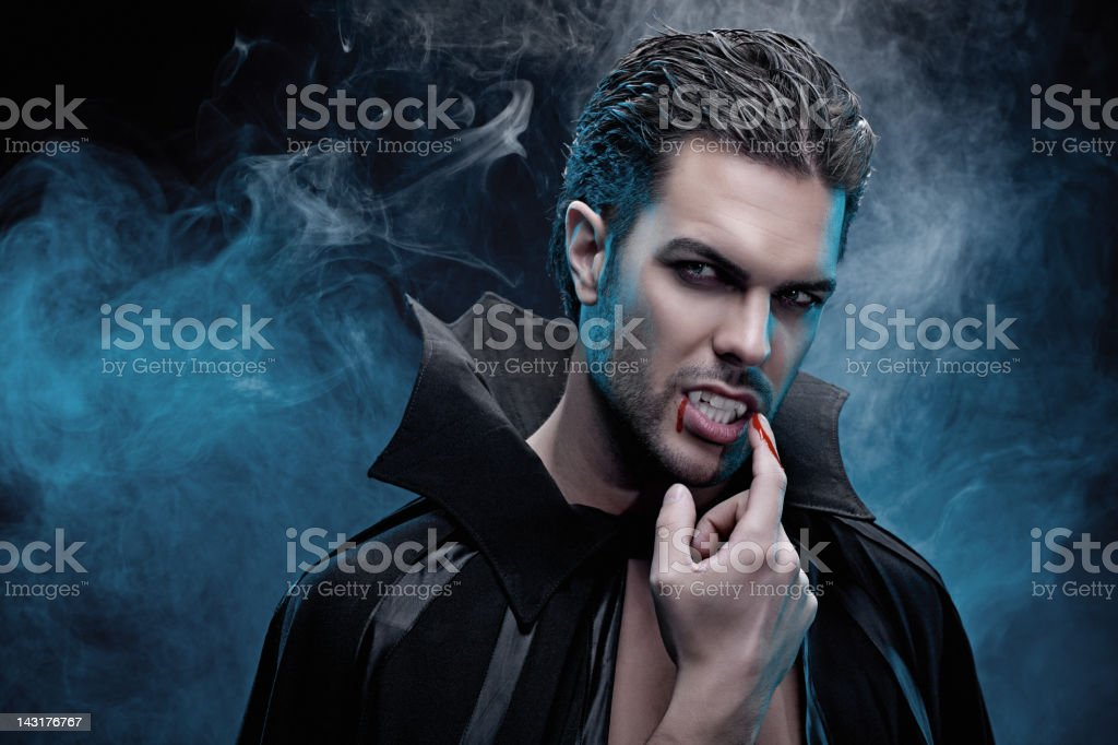 Vampire tasting blood from his finger stock photo